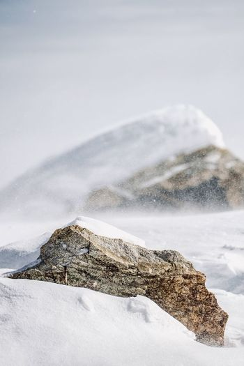 Scenic view of snow covered rock against sky