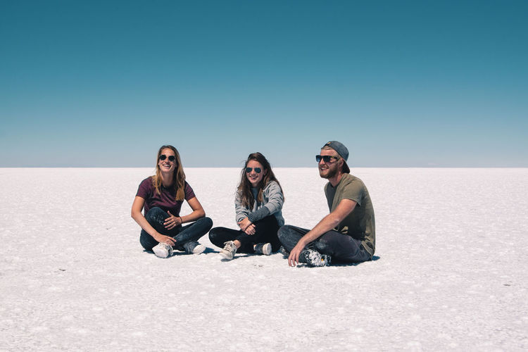 Young friends sitting on salt flat against clear sky