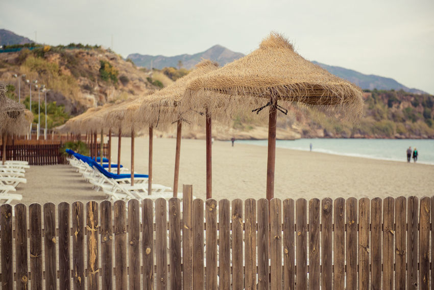 Parasols and empty deckchairs on the Nerja beach. Spain Andalusia Beach Beach Umbrellas Coast Day Deck Chairs Deckchairs Europe Fance In A Row Mediterranean Sea Mountain Nature Nerja No People Outdoors Parasols Sand Seashore Seaside SPAIN Straw Parasol Tourist Resort Travel Destinations Winter