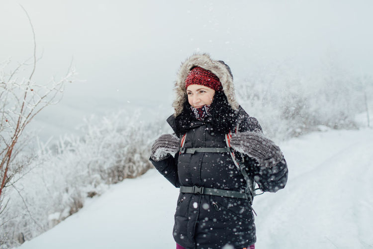 Woman In Warm Clothing Standing On Snow