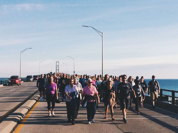 """Macinac Bridge walk in Mackinaw City on Sperember 5th 2016. What a blast! As we're walking everyone asks their neighbors """"how many beers have you had?"""" As the bridge sways back and forth making you lose your balance. Street Light Large Group Of People Men Walking Motion Road Transportation Sky Clear Sky Cloud Day Group Of People City Life Person Casual Clothing In A Row Outdoors Rush Hour Macinac Bridge Walk Bridge Walk Mackinaw City, MI Bridge Annual Street Photography Street"""