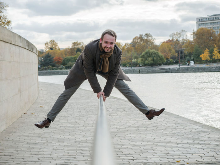 Portrait Of Smiling Man Jumping Over Railing