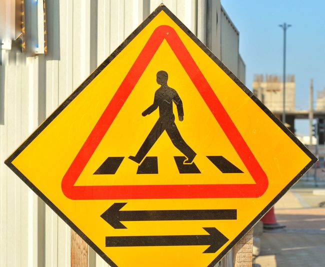 Pedestrian Safety Sign Yellow Pedestrian Safety Sign Human Representation Communication Representation Yellow Warning Sign Information Sign Information Guidance Male Likeness Close-up Symbol No People Triangle Shape Road Road Sign Shape Day Arrow Symbol Directional Sign