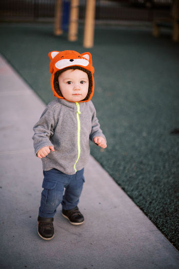 Portrait of boy standing on footpath