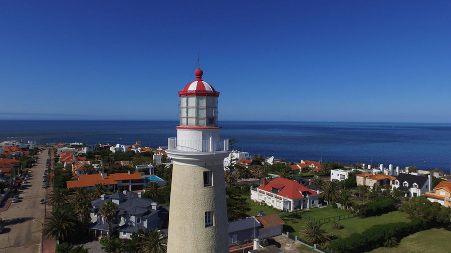 Lighthouse by sea against buildings in city against clear blue sky