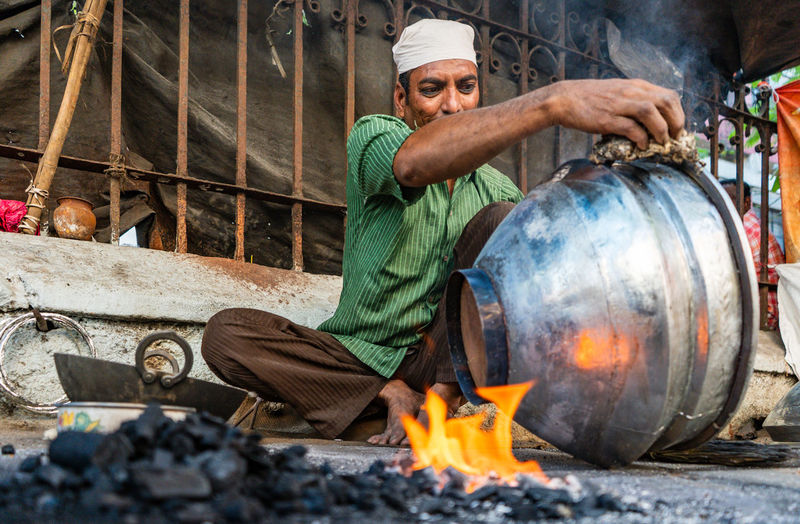 An environmental portrait of a steel-smith SonyA7III Sonyalpha Streetphotography Street Street Photography India Man Work Lifestyles Men Flame Burning Working Heat - Temperature Occupation Blacksmith  Fire Pit Bonfire Fire - Natural Phenomenon Lit Fire Heat Ash Smoke - Physical Structure