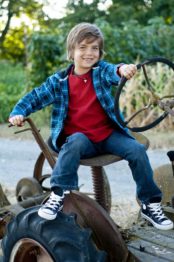 Boy on tractor Childhood Child Front View Casual Clothing Real People One Person Looking At Camera Day Smiling Portrait Sitting Full Length Lifestyles Happiness Outdoors Tractor Steering Wheel Seat Tire Old-fashioned Plaid Shirt  Blue Red Shoes