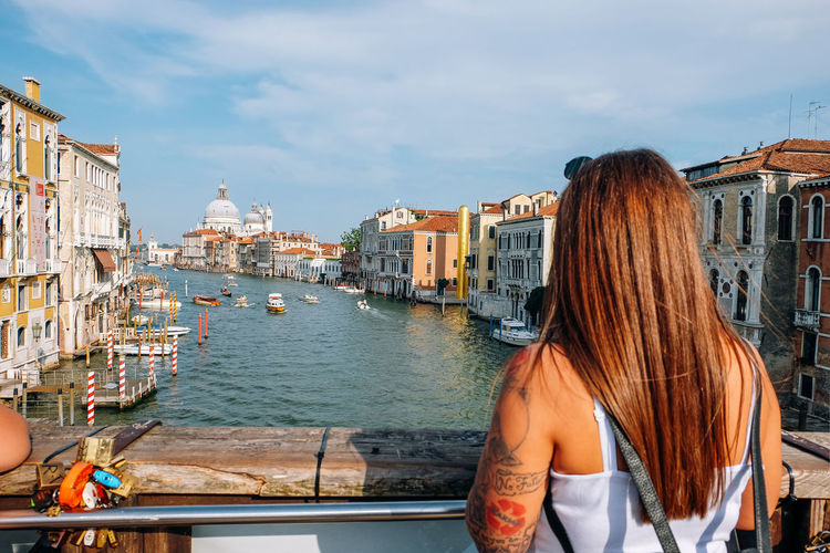 young woman looking at the view of venice in Italy Venice Venice, Italy Italy Travel Travel Destinations Summer City Water Architecture Built Structure Building Exterior Sky Rear View Real People Adult Hairstyle One Person Lifestyles Hair Outdoors Canal Looking At View Tourist Woman Tourism