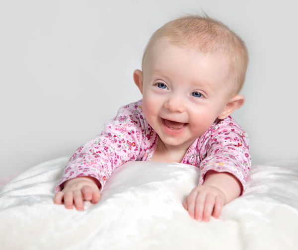 Close-up of cute baby girl in bed