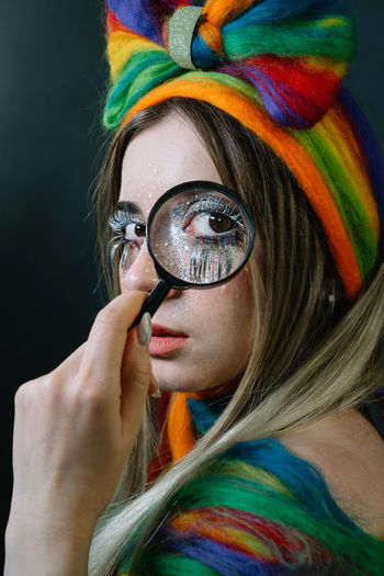 Close-up portrait of young female model holding magnifying glass against black background