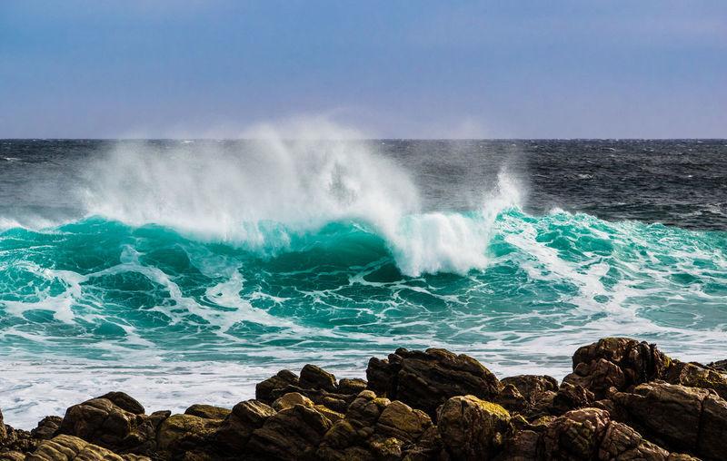 Waves Breaking Against Rocks In Sea Against Clear Sky