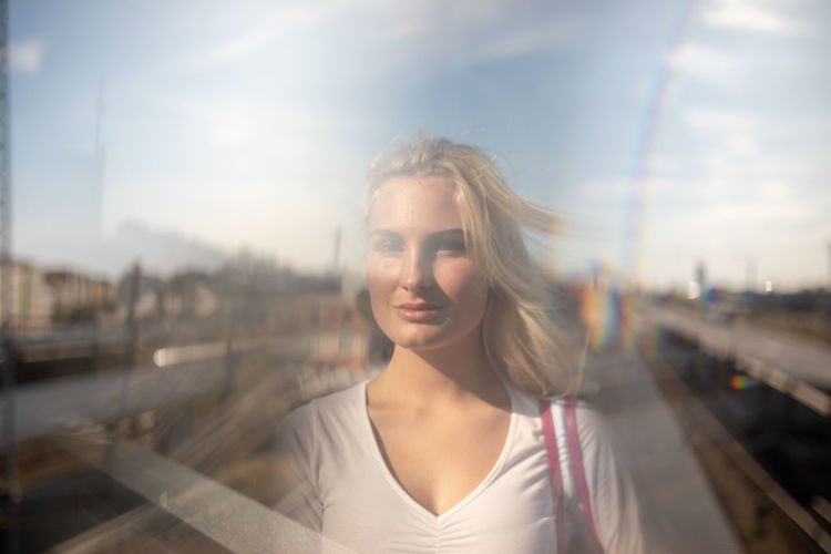 Double exposure image of young woman with railroad tracks against sky