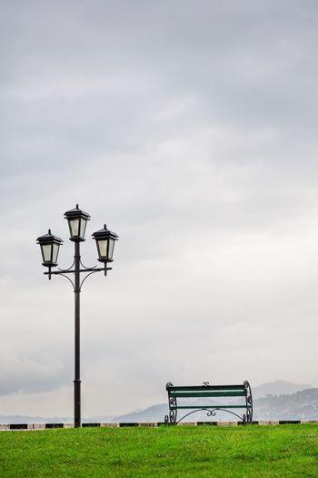 Street light on bench on field against sky