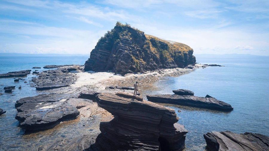 High angle view of man standing on rock formation at beach