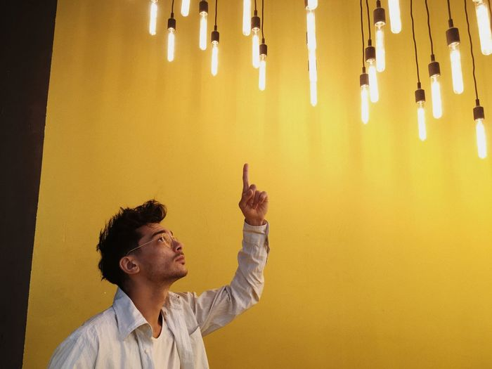 Man pointing at illuminated pendant lights in home