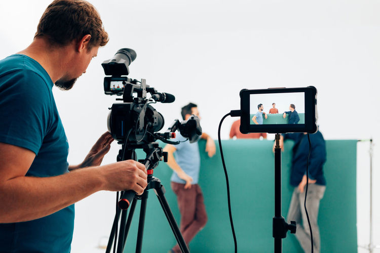 Professional camera operator filming video with three actors in the studio
