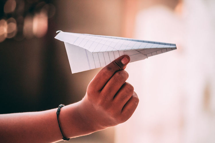 Cropped hand holding paper plane