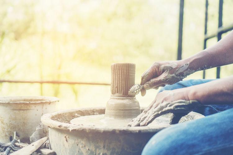 Cropped Image Of Man Making Pot Outdoors