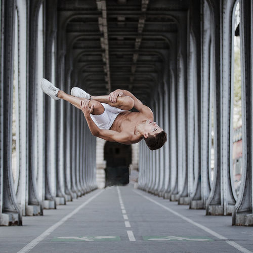 Shirtless Man Jumping Below Bridge In City