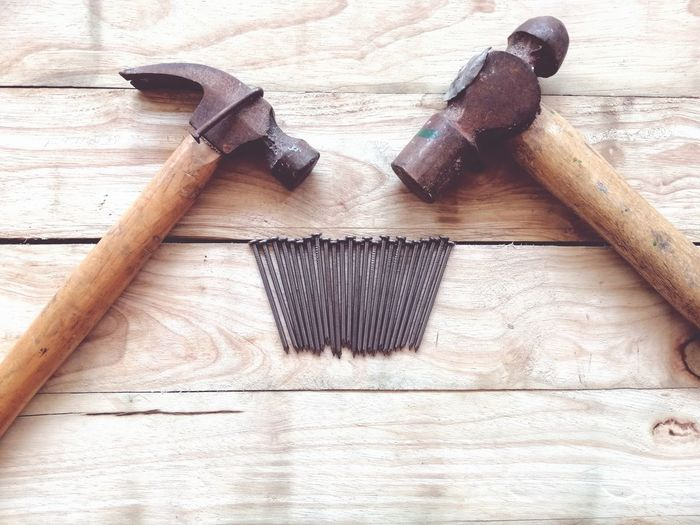 High angle view of nails and hammers on wooden table