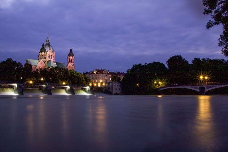 St. Luke's Church on the banks of river Isar in Munich, Germany Illuminated Architecture Sky Water Night Waterfront Built Structure River Building Exterior Tree City Outdoors No People Cloud - Sky Long Exposure City Lights City Lights At Night