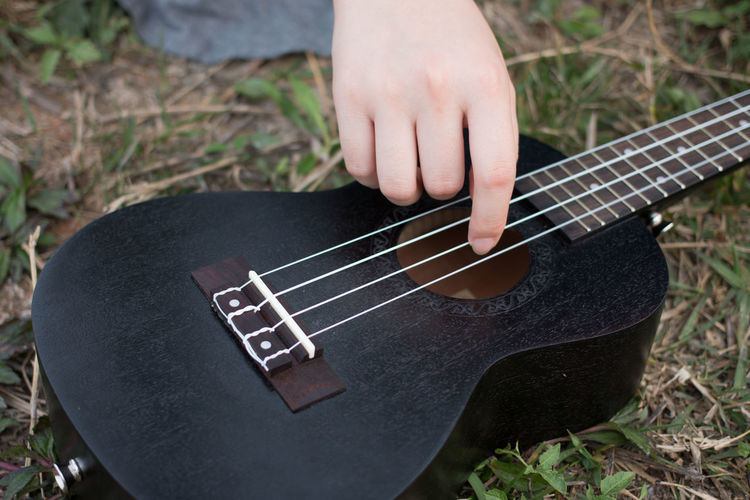 Close-up Cropped Field Focus On Foreground Grass Guitar High Angle View Hobbies Holding Leisure Activity Lifestyles Men Music Musical Instrument Part Of Person Working Showcase April