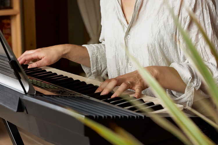 Female musician playing the digital piano or electronic keyboard at home. music education.