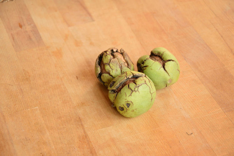 Walnuts (Juglans regia) in shell on the table Juglans Regia Food And Drink Healthy Eating Wellbeing Food Freshness Indoors  No People Table Close-up Wood - Material Fruit High Angle View Walnuts Green Color Organic