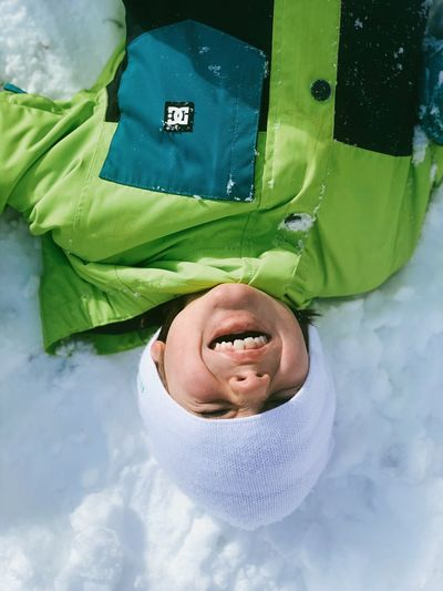 First snow Upside Down Snow Hat Light Sun DC High Angle View Green Color Lying Down Winter Representation Real People Day Directly Above Lying On Back Cold Temperature Smiling Warm Clothing