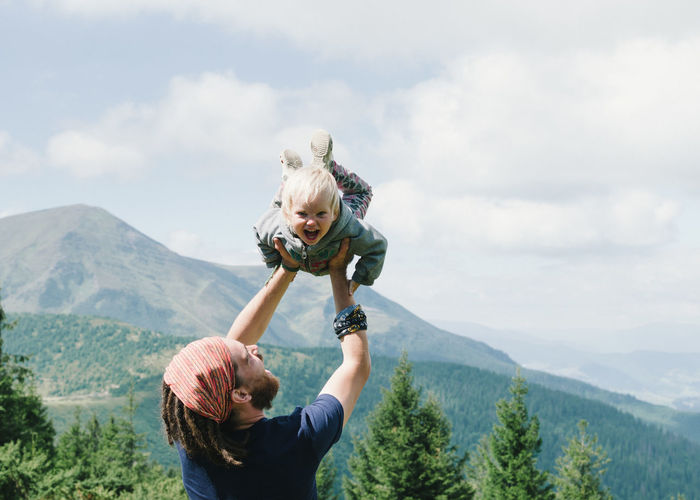 Father Lifting Daughter On Mountain Against Sky