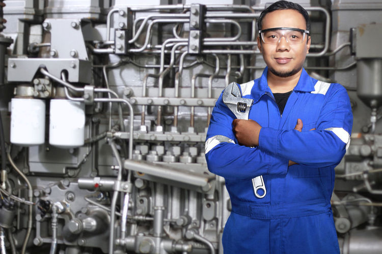Portrait of worker with arms crossed standing by equipment in factory