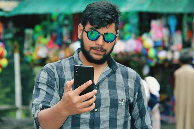 Young man wearing sunglasses using mobile phone while standing in market