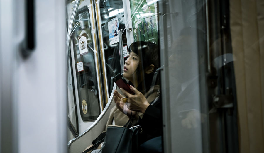 Young woman looking away sitting in subway train
