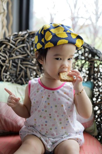 Portrait Of Cute Girl Eating Cracker While Sitting On Chair At Home