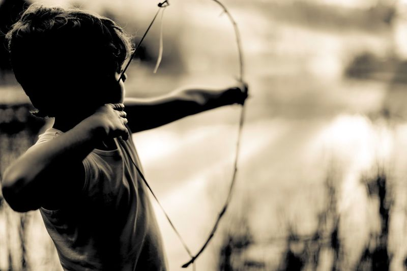 Side View Of Boy With Bow And Arrow