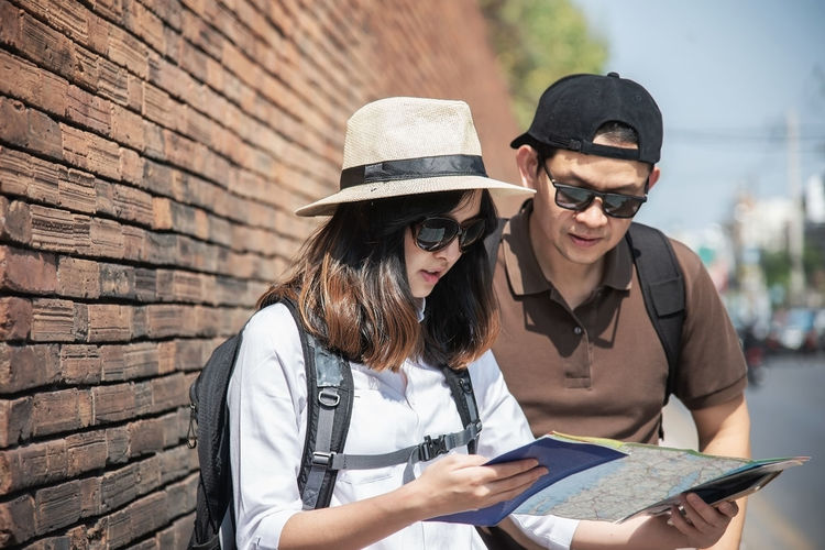 Man discussing map with woman while standing in city