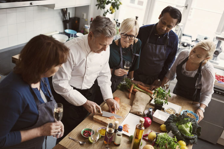 Group of people having food in kitchen