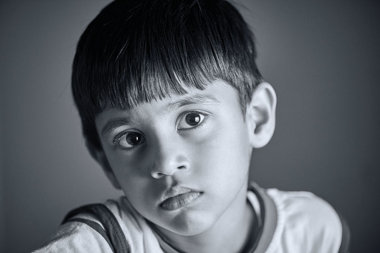 Close-up portrait of boy against gray background