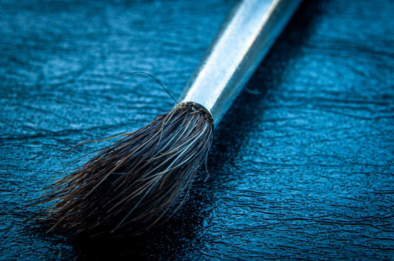 High angle view of paintbrushes on blue table