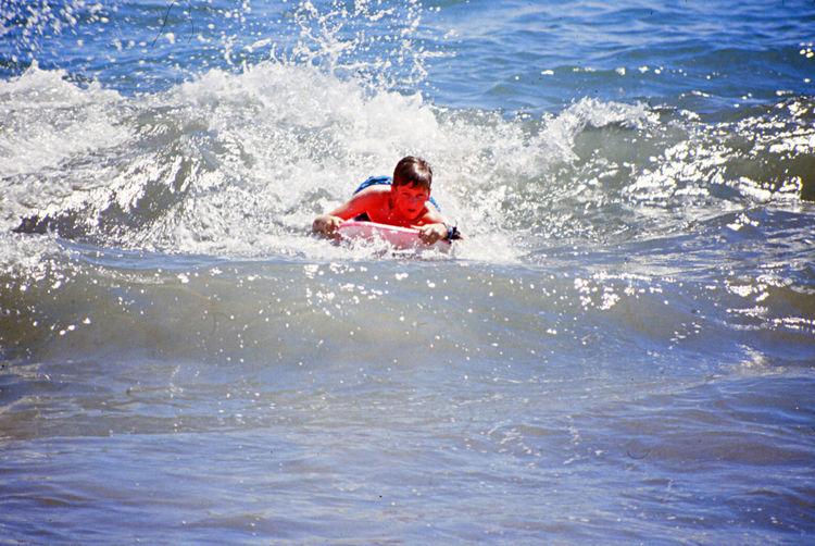 Boy surfboarding in sea