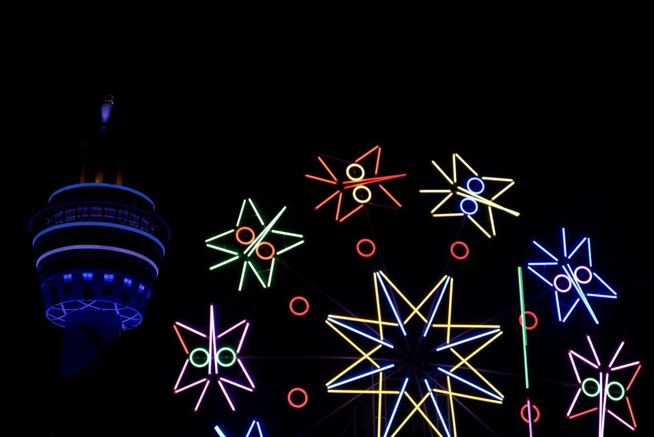 ILLUMINATED CHRISTMAS LIGHTS AT NIGHT AGAINST STAR FIELD