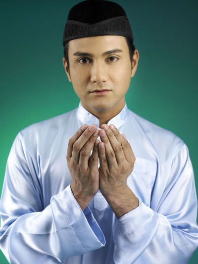 Close-up portrait of man praying against green background