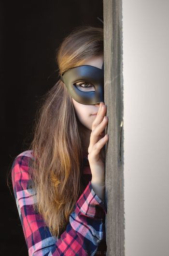 Portrait of woman wearing eye mask while standing against wall