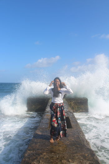 Full length portrait of woman standing on pier with waves splashing in sea against blue sky