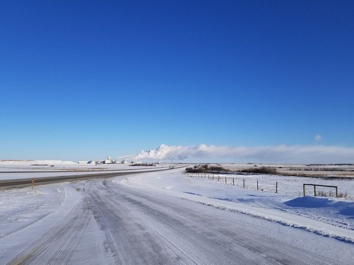Road by snow covered land against blue sky