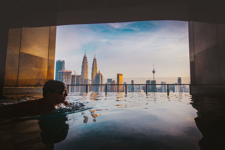 Man Swimming In Infinity Pool Against Buildings