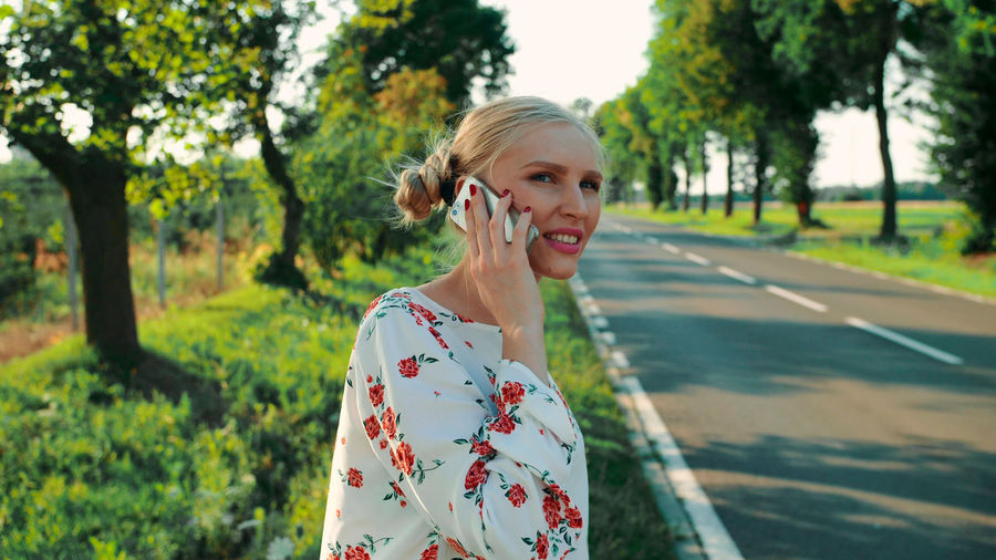 Portrait of smiling young woman standing on smart phone