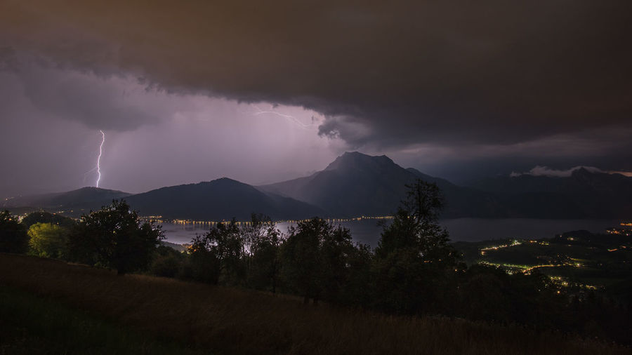 Panoramic view of lightning over mountain against sky at night