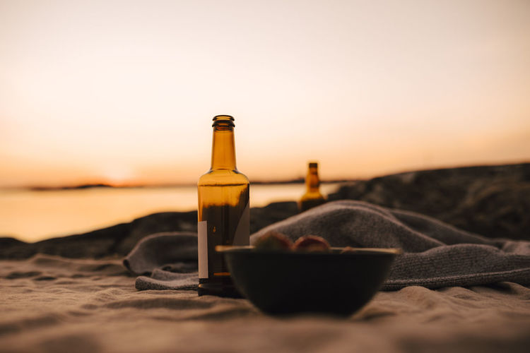Close-up of beer bottle on beach against sunset sky