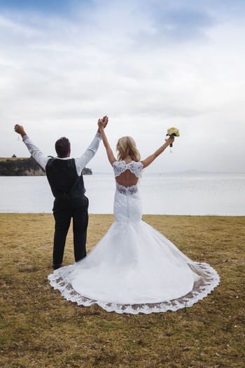 Newlywed Couple Standing With Arms Raised At Lakeside